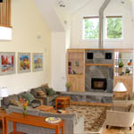 Living room comfy chairs and couches around a wood burning fireplace.